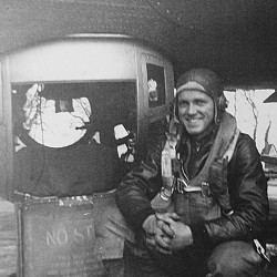 All smiles after completing his 35th and final bombing mission against Nazi Germany, Wayne Dennison poses beside his ball turret in mid-June 1944.