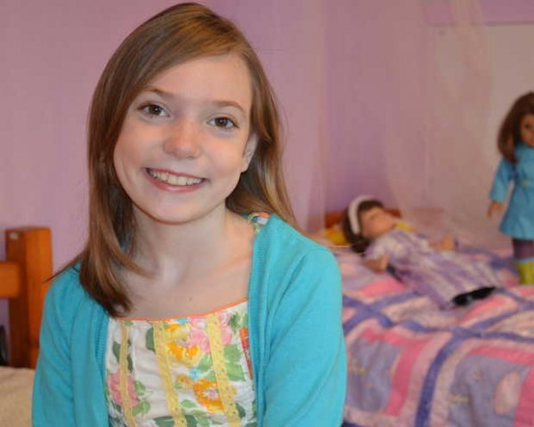Kaylynn Johnson of Norway poses in front of her American Girl dolls. She is a finalist in the video story contest &quotCaroline's Share the Hero in You&quot by American Girl. She is collecting cereal boxes to be used in Haiti to make jewelry and other items so parents can help pay for food, shelter and education for their children.
