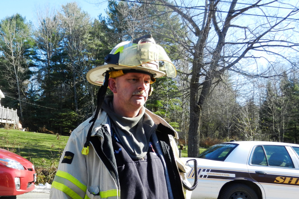Orrington Fire Chief Mike Spencer talks with media at the scene of a fire on Dow Road in Orrington on Saturday.