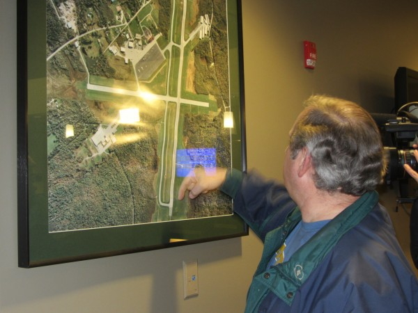 Knox County Regional Airport Manager Jeffrey Northgraves points to the direction that the Cessna 172 was heading before it crashed on the runway. The aerial picture of the airport is in the lobby of the airport terminal.