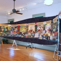 Volunteers at the Castine Historical Society hang the Castine Bicentennial Quilt, created by community members and donated to the historical society in 1996. The quilt will be on view at an open house from 11am-3pm on December 1, 2012.