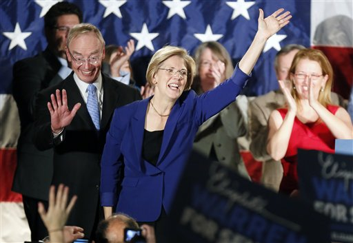 Democrat Elizabeth Warren, center, waves to the crowd with her husband Bruce Mann, left,  during an election night rally at the Fairmont Copley Plaza hotel in Boston after Warren defeated incumbent GOP Sen. Scott Brown in the Massachusetts Senate race.