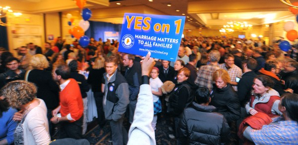 A supporter waves a sign during the Mainers United for Marriage campaign party at the Holiday Inn in Portland. Hundreds of people gathered to watch the election returns on Tuesday night.