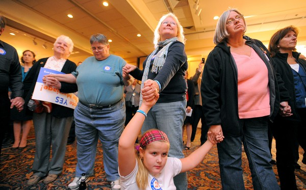 Ellie Kingman of Yarmouth joins hands with others during a prayer at the Mainers United for Marriage campaign party at the Holiday Inn in Portland. Hundreds of people gathered to watch the election returns on Tuesday night.