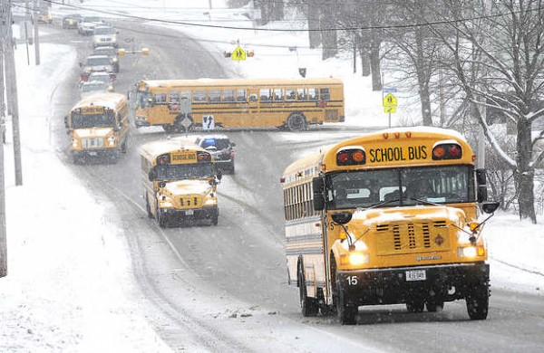 School buses make their way uphill on Court Street in Auburn at the end of the school day Monday as they leave Auburn Middle School during the snowfall.