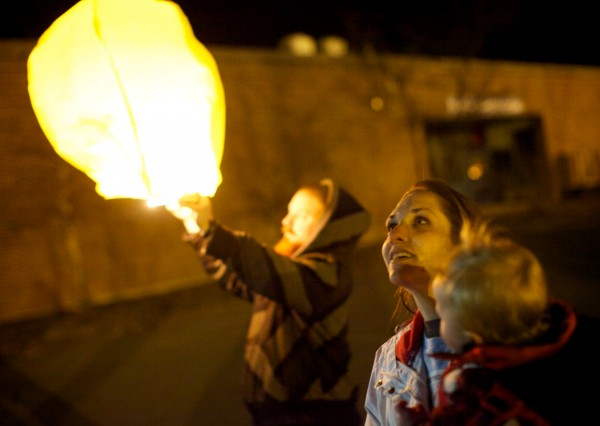 Trista Reynolds and her son, Raymond, watch paper lanterns lit to mark the one-year anniversary of Ayla's disappearance drift into the night sky in Portland on Saturday.