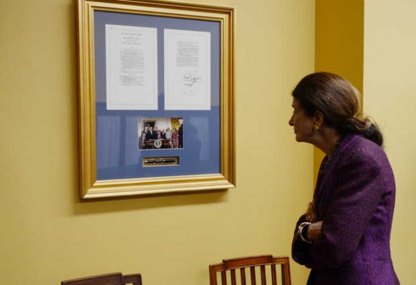 U.S. Sen. Olympia Snowe looks over one of the many bills she worked on that was signed into law. Senators who co-sponsor bills are photographed with the president and receive a pen used by him to sign the bill into law. This framed copy of the bill, photograph and the pen is the Lilly Ledbetter Fair Pay Act signed in 2009. The law allows workers to sue in cases of pay discrimination based on gender. The bill is considered landmark because it helps ensure women are paid wages equal to men when they are performing the same job.