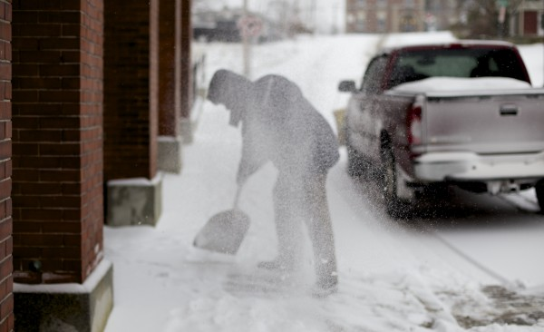 Mark Perry shovels snow away from the front of his office on Columbia Street Thursday morning in Bangor. A storm that hit Maine on Thursday could bring as much as 18 inches of snow to some areas.