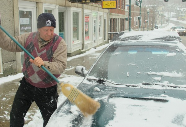 Billy Chamberlain, 66, of Ellsworth uses a broom to sweep the powdery snow off his Subaru on Main Street in Ellsworth on Thursday, Dec. 27, 2012. Chamberlain said the broom is the best tool for clearing snow off his car because the wooden handle keeps your hands warm.