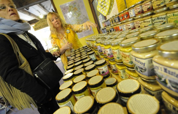 Karen Raye of Raye's Mustard in Eastport helps Linda McKee (left) of Florida with choosing from one of many mustard varieties at the store. McKee was among the residents aboard The World who debarked the 644-foot vessel to enjoy sightseeing and shopping in Eastport Tuesday, Oct. 9, 2012.