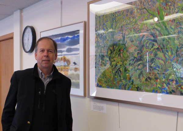 Carl Little, author of many Maine art books, stands in the Ellsworth Library's downstairs gallery.