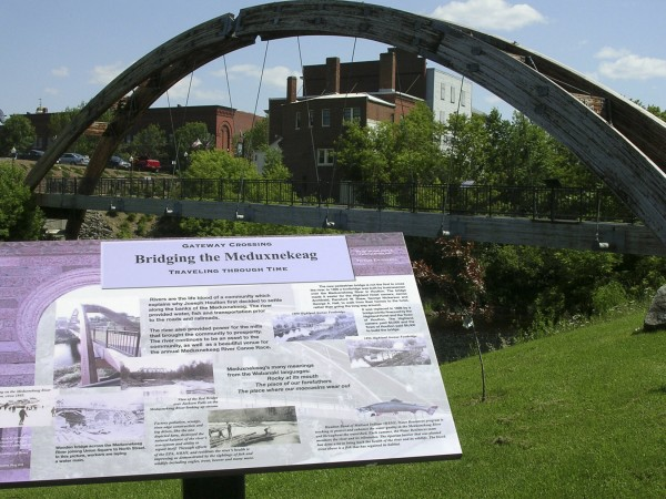 Informational storyboards, such as this one next to the Gateway Crossing pedestrian bridge across the Meduxnekeag River, assist people taking a walking tour of Houlton.