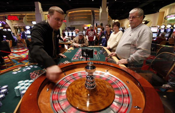 A dealer (left) places a ball on a spinning roulette table at Bangor's Hollywood Casino in March 2012.