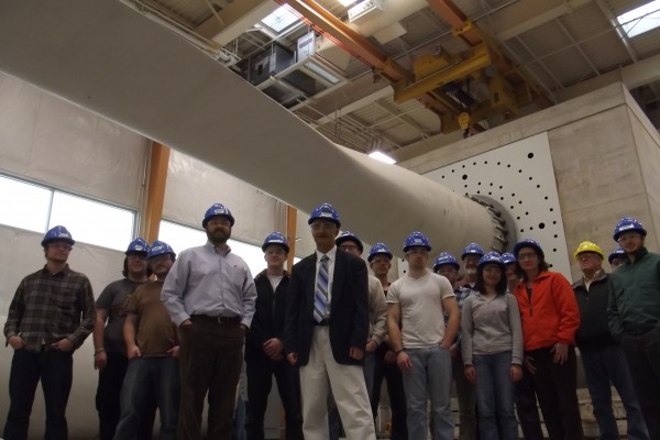 Habib Dagher, director of the UMaine Advanced Structures and Composites Center (front right), and Jake Ward, assistant vice president for research, economic development and governmental relations at UMaine (front left), stand with members of deep water offshore wind energy development team stand under a 121-foot turbine blade undergoing stress testing at the UMaine research facility on Friday, Dec. 7.