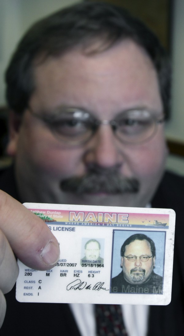 Rep. Richard Cebra, R-Naples, holds up his drivers license in his office at the State House in Augusta in 2011.