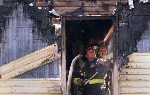 Firefighters search for hot spots inside the walls of a home that burned early Sunday morning, Dec. 23, 2012.
