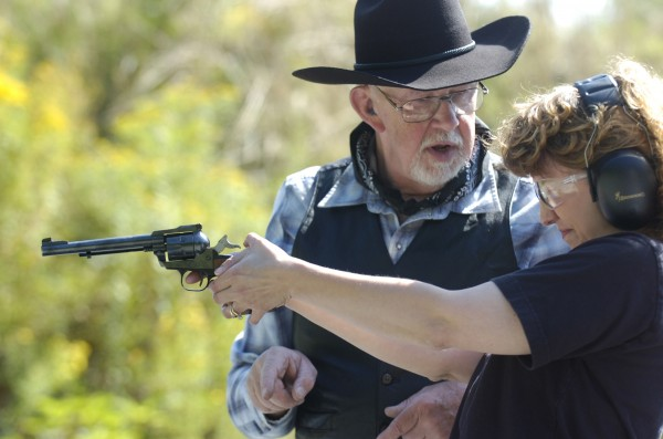 Under the careful tutelage of Charlie Rumsey, participant Joelle Milliken of Bangor gets ready to fire a pistol provided at the &quotIntroduction to Shooting Sports&quot cowboy action pistol and rifle event at the Hampden Rifle & Pistol Club on Aug. 8, 2009.