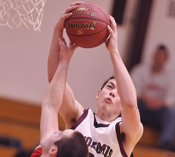 Nokomis' Andrew Cartwright gets both hands on a rebound over Camden Hills' Connor Hart during a game last season. Both players return this season to help their teams seek a tourney berth.