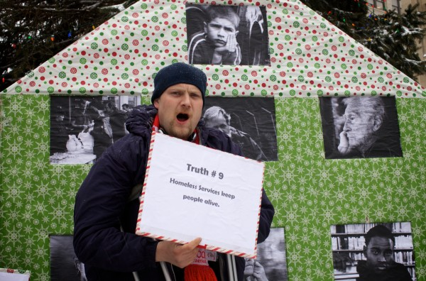 Rob Dalrymple reads a &quottruth&quot about homelessness from an Advent calendar-like display in Portland's Monument Square on Monday Dec. 17, 2012, during an event put on by Homeless Voices for Justice.