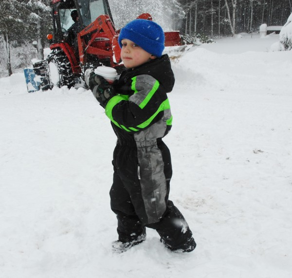 Ethan Malmborg has the right idea on how to spend a snowy day. The 5-year-old enjoyed a cup of hot cocoa while his father Kris Malmborg uses a tractor to snow blow a Fort Kent driveway.