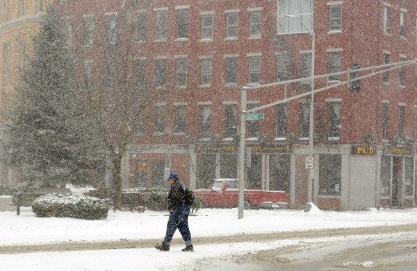 A pedestrian crosses Main Street through the blowing snow in downtown Bangor on Thursday morning.