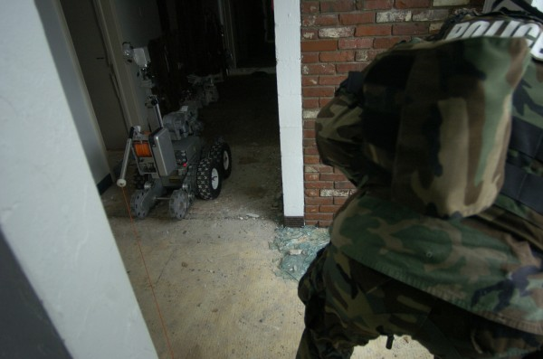 Wielding assault weapons and protective gear, a  Bangor police officer clears the way as the department's robot approaches after providing surveillance in a hallway during a media demonstration in February 2007.
