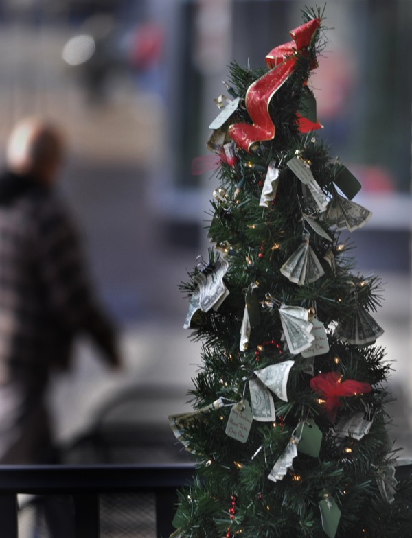 Dollar donations are clipped to the Bangor Elves' small holiday Giving Tree in downtown Bangor in December 2011.