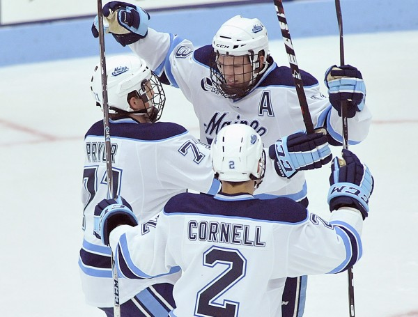 University of Maine senior left wing and assistant captain Spencer Abbott (top) celebrates his first goal of the game with Nick Pryor and Mike Cornell during an October 2011 6-3 win over Northeastern. Abbott had a pair of goals and an assist.