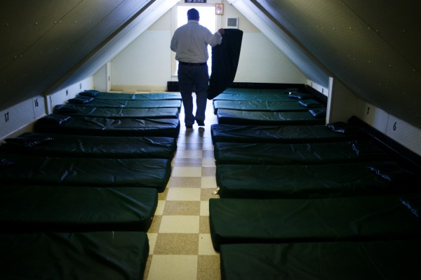 Josh O'Brien, director of Portland's Oxford Street Shelter, moves and checks mats on the third floor Wednesday Dec. 12, 2012, during his daily walk through the facility. The third floor alone has enough beds to consider it the largest dry shelter in the state.