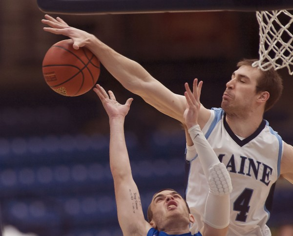 University of Maine men's basketball player Mike Allison (44) gets a block on FGCU player Brett Comer in the first half of their game in Orono on Saturday, Dec. 22, 2012.