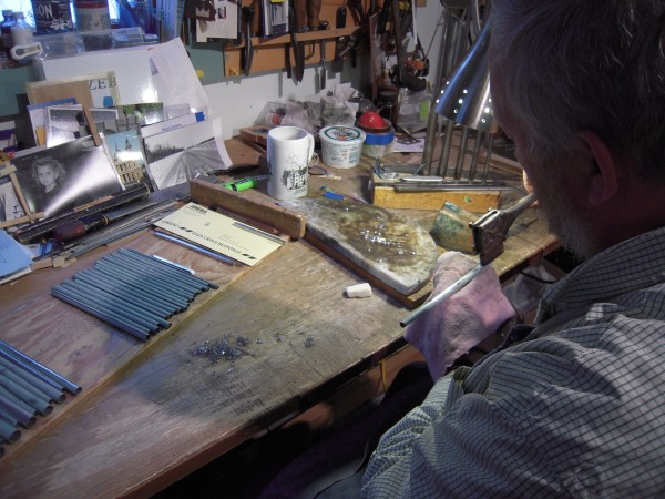 Bright beads of solder float on a flat slab of marble as Stephen Boody of New Sweden seals the fine seam on one of 256 pipes he is making for a pipe organ to be installed in North Carolina.
