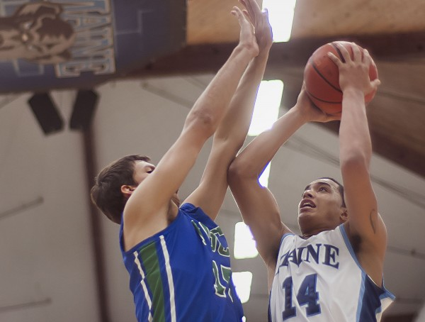 University of Maine men's basketball player Justin Edwards (14) shoots around FGCU player Filip Cvjeticanin in the second half of their game in Orono on Saturday, Dec. 22, 2012.