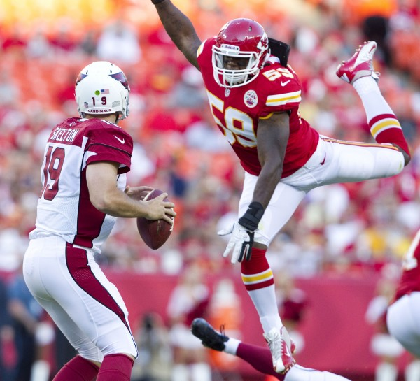 Arizona Cardinals quarterback John Skelton (19) prepares to deliver a pass as Kansas City Chiefs linebacker Jovan Belcher (59) takes to the air while defending the play in the first quarter on August 10, 2012, at Arrowhead Stadium in Kansas City, Missouri.