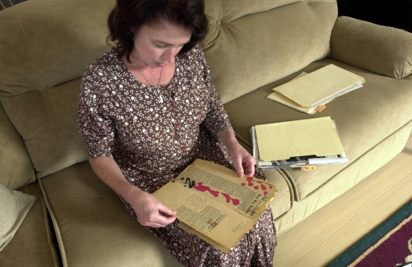 In June 2003, Sherry Sullivan looks through some government documents about her father, Geoffrey Sullivan, who disappeared on Sept. 24,1963 during a flight to Honduras.