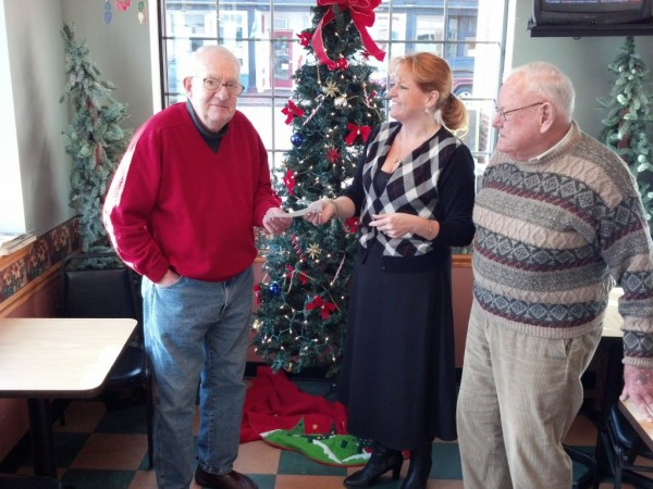 Members of a Bath-area men's social group called the ROMEOs, or Retired Old Men Eating Out, recently donated $650 to the Bath Area Food Bank. Shown last week are Mark Smith (left) and Vincent Messler (right) of the ROMEOs along with Kimberly Gates, coordinator of the food bank.