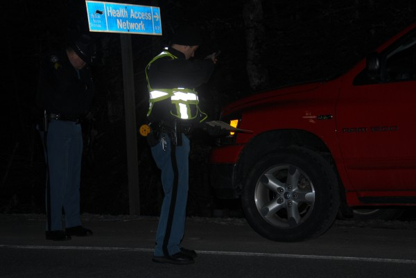 State police Sgt. David Millett and Trooper Larry Anderson (right) examine the front end of a pickup truck that hit a pedestrian on Route 2 in Enfield on Sunday, Dec. 16, 2012.