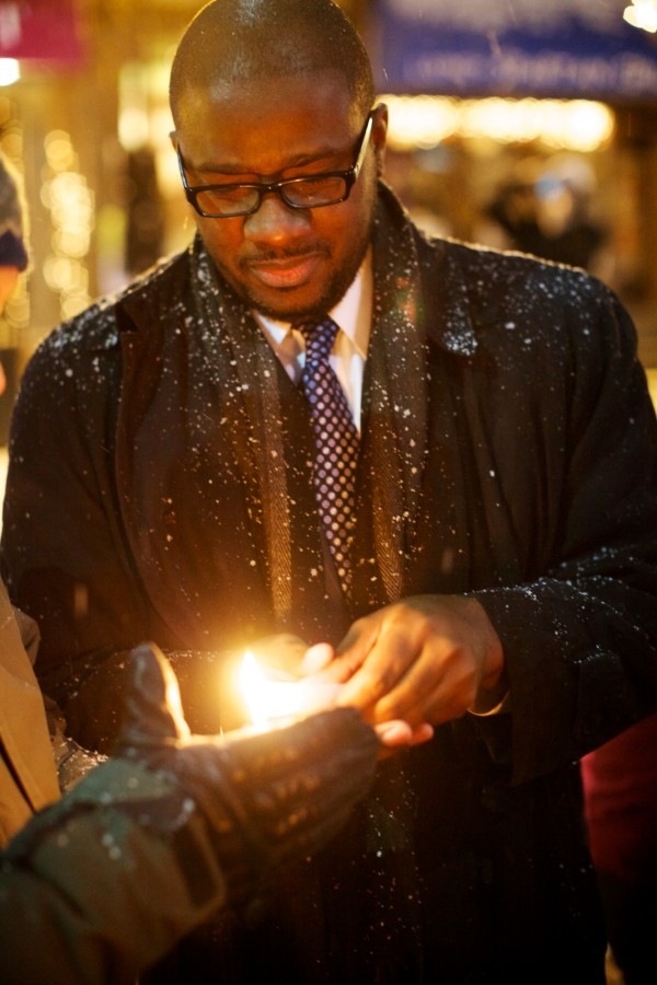 Portland School Superintendent Emmanuel Caulk lights a candle at the start of a vigil in Monument Square on Sunday night Dec. 16, 2012. The vigil was organized by Maine Citizens Against Handgun Violence in response to the Connecticut school shooting Friday.