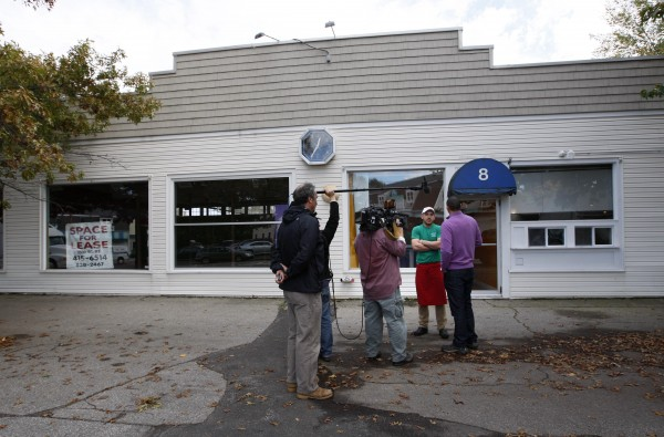 A pizzeria worker is interviewed by a TV crew in front of the former fitness studio where prostitution has been alleged to have occurred in Kennebunk on Friday, Oct. 12, 2012.