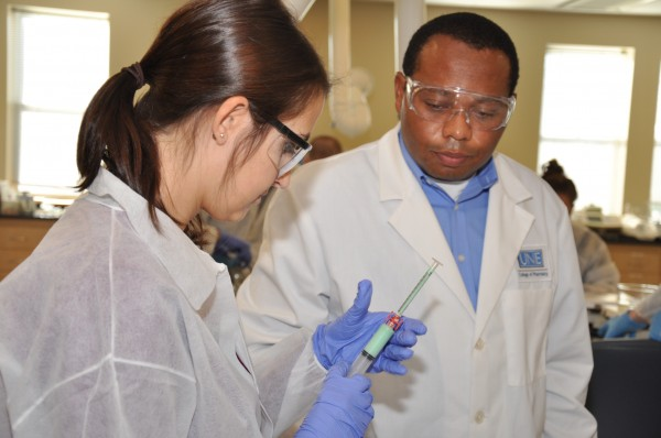 UNE College of Pharmacy students Katelyn Richard and Okechukwu Emmanuel learn how to formulate veterinary medications in a lab on the Portland campus.