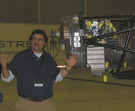 Richard Schwartz, powerplant engineer, gestures toward the Honeywell turbo-prop engine that will power Kestrel's newest plane on Monday, Dec. 11, 2012.