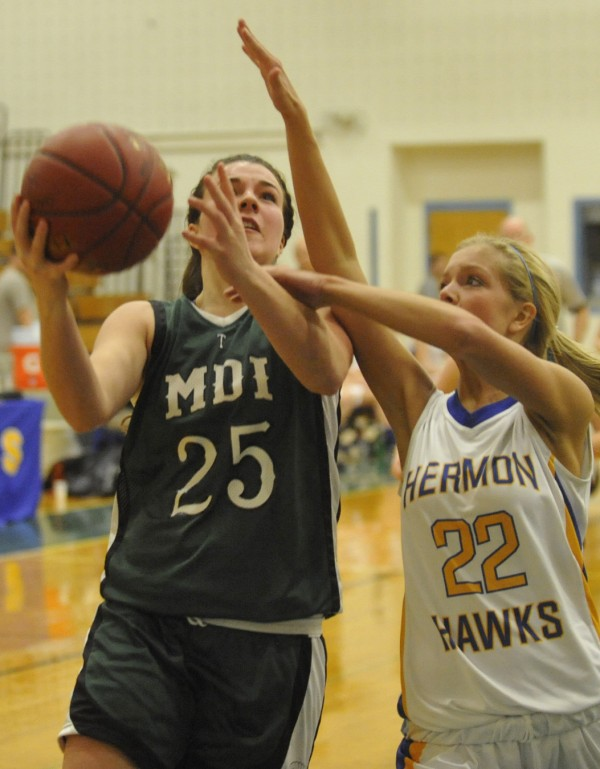 MDI's Hannah Shaw (25) takes it to the bucket with pressure from Hermon High School's Britney Hamlin (22) at Hermon High School in December 2011.