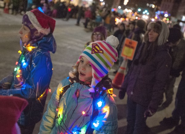 Bailey and her family join the many spectators along the curb on Main Street as the Festival of Lights parade passes by in downtown Bangor on Saturday.