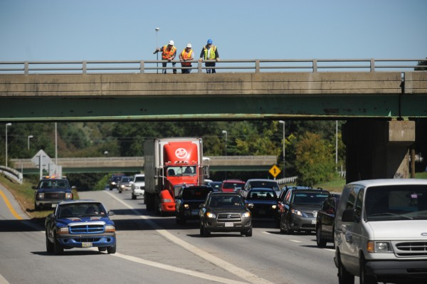 A Bangor Water Dept. employee and Maine DOT employees stand atop the Union St. Bridge as they size up the structural damage to the bridge after a truck's forklift and steal beam frame payload heading I-95-southbound failed to completely clear the overpass around 11:30 am Thursday, Sept. 20, 2012.