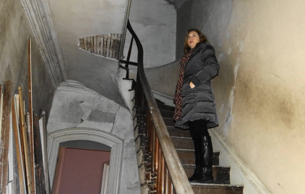 Real estate agent Tara Roy climbs the curved staircase in the Franklin Treat house in Frankfort.