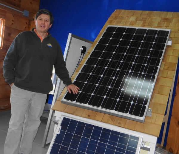 Chuck Piper poses with one of the kinds of photovoltaic panels he sells at his Searsport business, Sundog Solar Store.