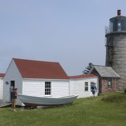 Tourists explore the grounds around Monhegan Island Lighthouse in March. The island community has a year-round population of about 70.