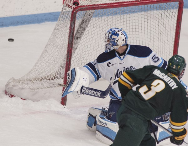 Maine hockey goalie Martin Ouellette (51) gets a pad on a shot wide as Vermont forward Chris McCarthy  (3) chases the rebound in the second period of their game in Orono on Saturday.