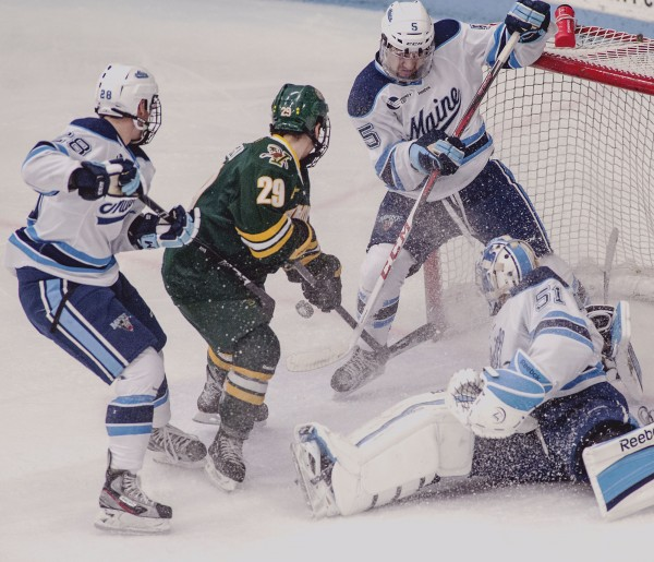 Maine hockey goalie Martin Ouellette (51) and forwards Andrew Cerretani (5) and Will Merchant (28)  scramble to get a loose puck away from Vermont player Robert Polsello (29) in the third period of their game in Orono on Saturday.