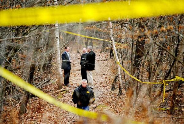Lewiston Police Chief Michael Bussiere (back left), Lisbon Police detective Bernie McAllister (back center), an unidentified man and Lewiston detective Roland Godbout (foreground) investigate along a dirt trail where the remains of a body were found in Lisbon on Tuesday, Dec. 4, 2012.
