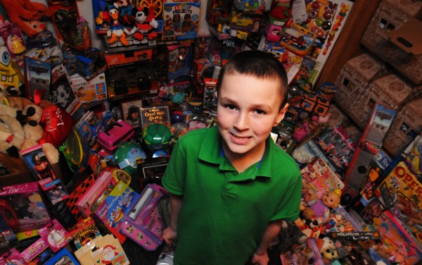 Brayden Mott of Orrington stands surrounded by the almost 2012 toys he has amassed to be given to needy children in the greater Bangor area.